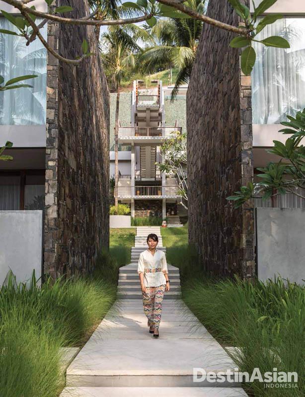 Seorang staf Svarga Resort dengan latar belakang bangunan megah.