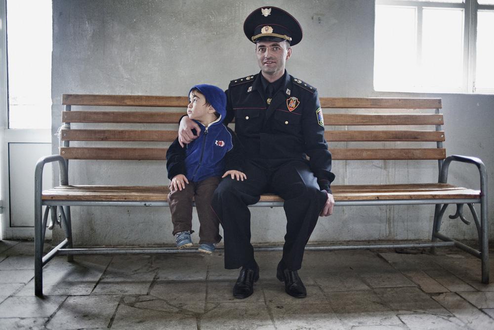 Seorang polisi militer dan putranya tengah menanti bus di terminal di Stepanakert.