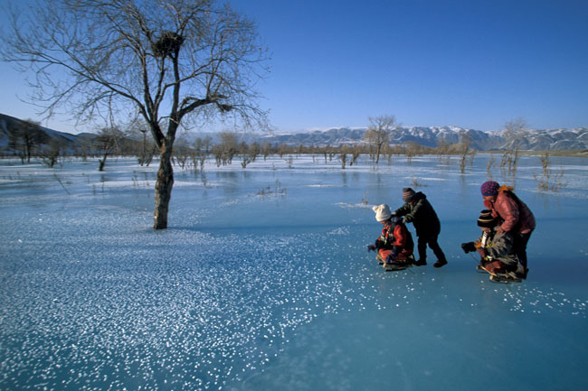 Anak-anak suku Kazakh bermain di atas Sungai Khovd yang membeku di dekat Tsengel. (Pegunungan Altay, Mongolia)