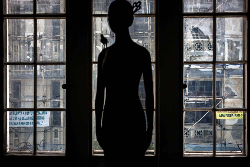 Pemandangan proses revitalisasi gedung tua tampak dari jendela di belakang patung