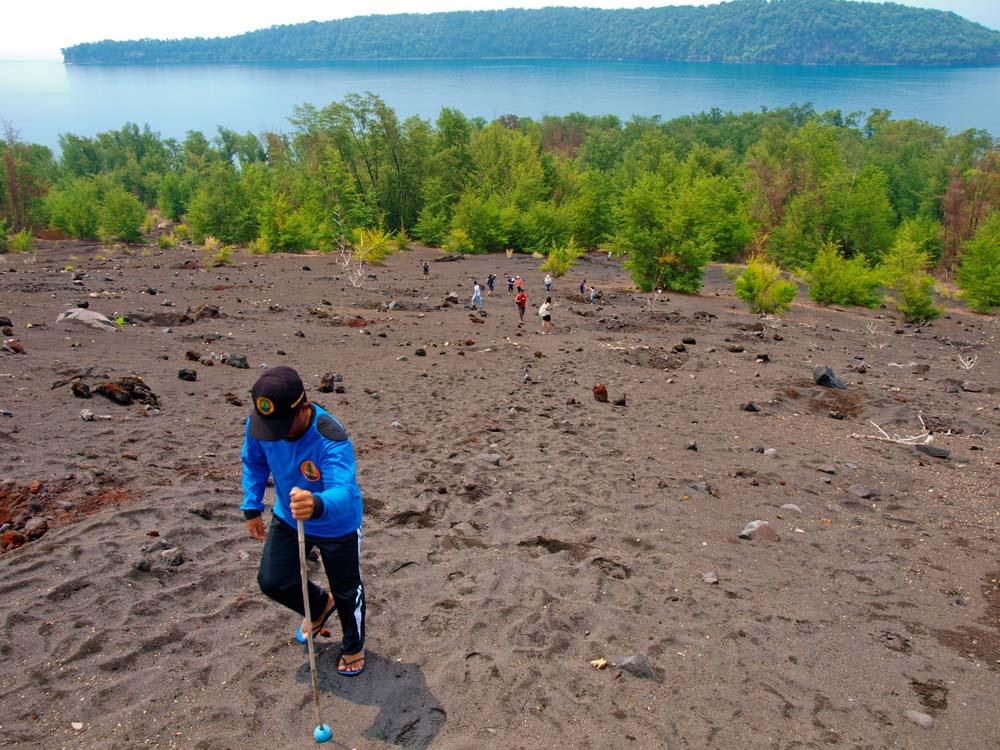 Jalur pendakian mendekati Patok Sembilan dengan latar belakang Pulau Rakata.