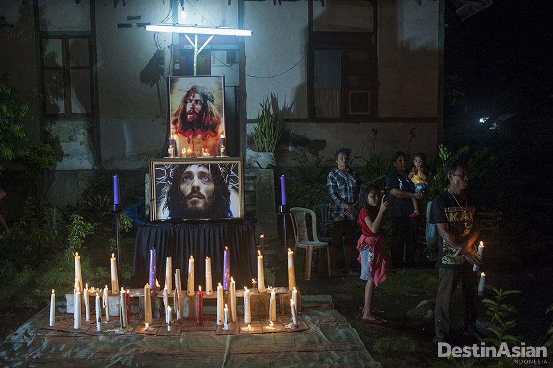 Warga Larantuka berdoa di depan rumah saat iring-iringan malam Jumat Agung melewati rumah mereka.