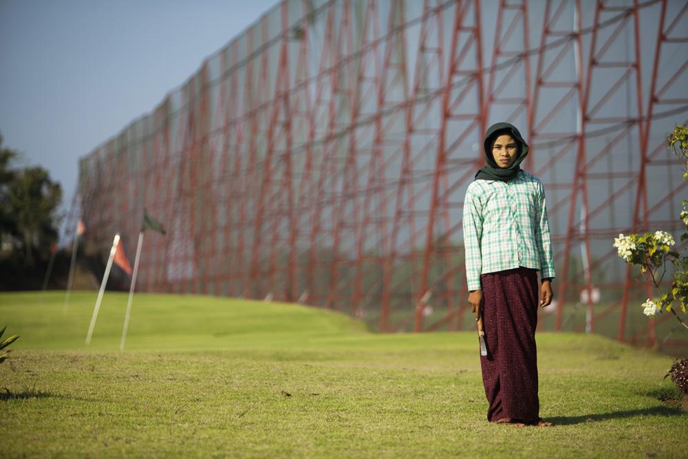 Seorang pekerja merawat lapangan golf di Naypyidaw.
