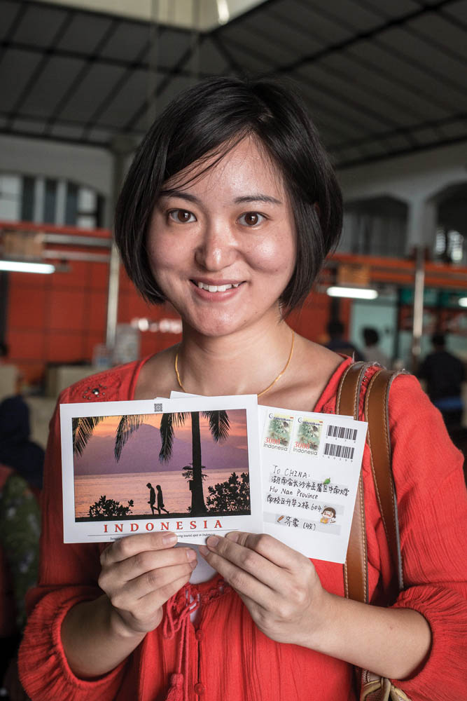 Seorang guru asal Tiongkok mengisi dan mengirimkan kartu pos dari Kantor Pos Kota Tua.