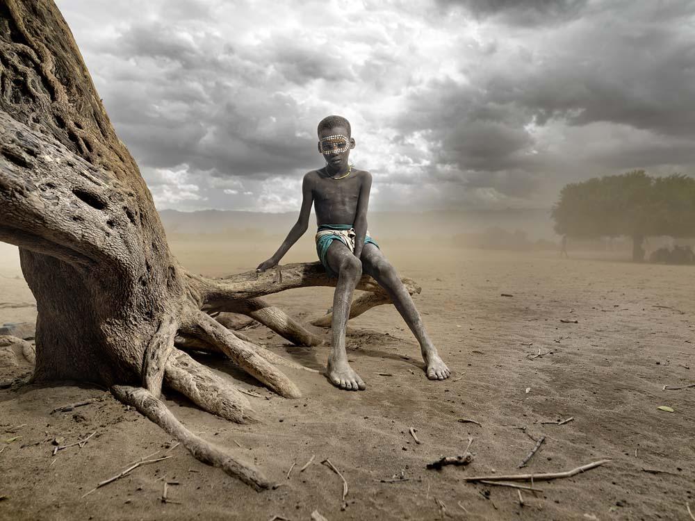 Seorang anak dari suku Arbore di Ethiopia tengah duduk di pohon dengan latar badai pasir. Foto karya Juan Carlos Ruiz Duarte.