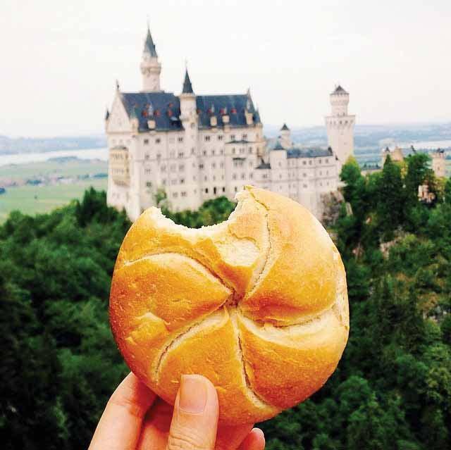 Menikmati roti breadroll di depan Kastel Neuschwanstein di Jerman. Kastel ini merupakan inspirasi dari kastel raja di cerita klasik Disney, Cinderella.