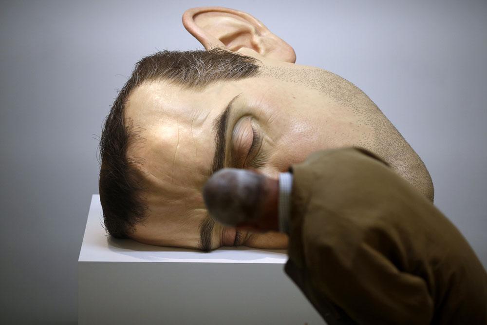 Salah seorang pengunjung memiringkan kepalanya untuk melihat patung MaskII lebih jelas. (Foto: THOMAS COEX/AFP/Getty Images)