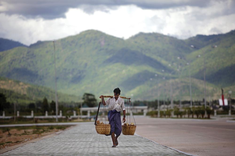 Seorang penduduk mengangkut puing-puing kayu di Naypyidaw. Foto: Getty Images.