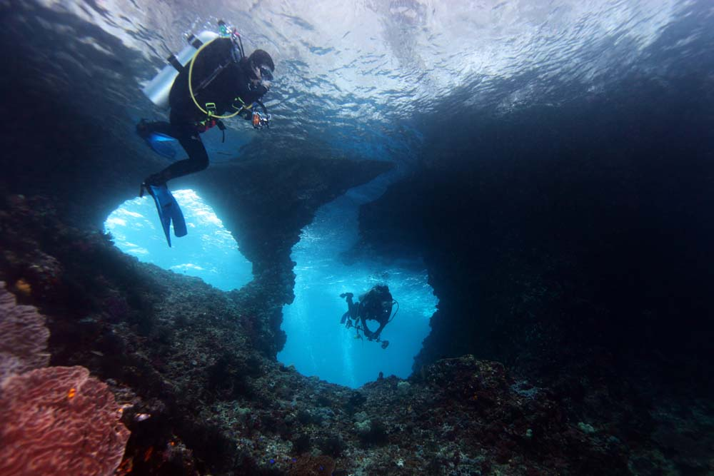 Penyelam melalui jendela-jendela dari batu karang di dive site Jendela, Raja Ampat.