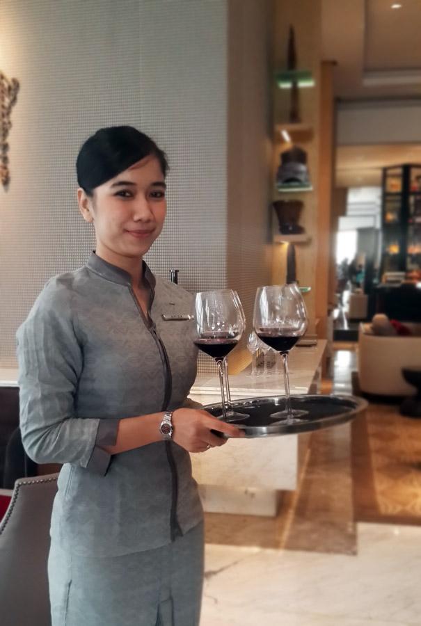 Pelayan akan menyajikan wine bagi para tamu.