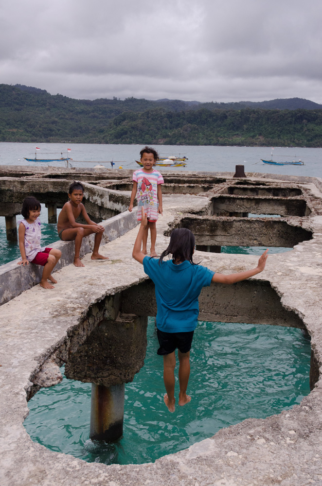 Anak-anak di Pulau Pisang tengah bermain di bekas dermaga yang rusak.