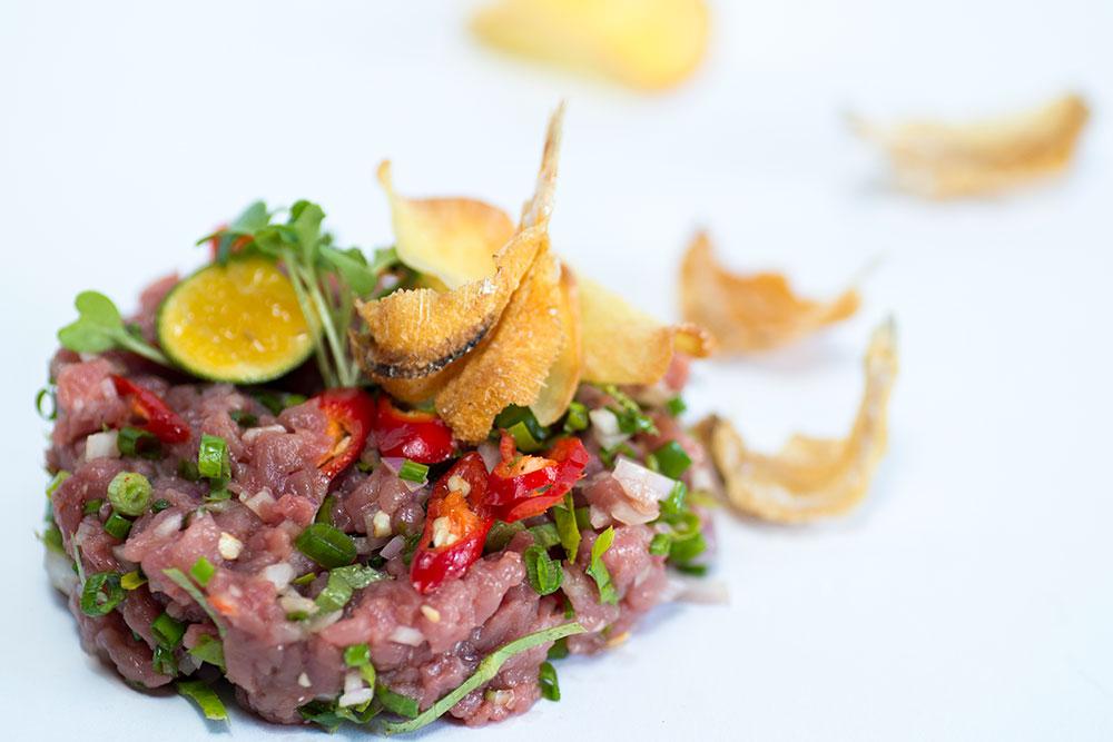 Beef tartar dengan sambal ulek, keripik singkong, dan ikan asin.