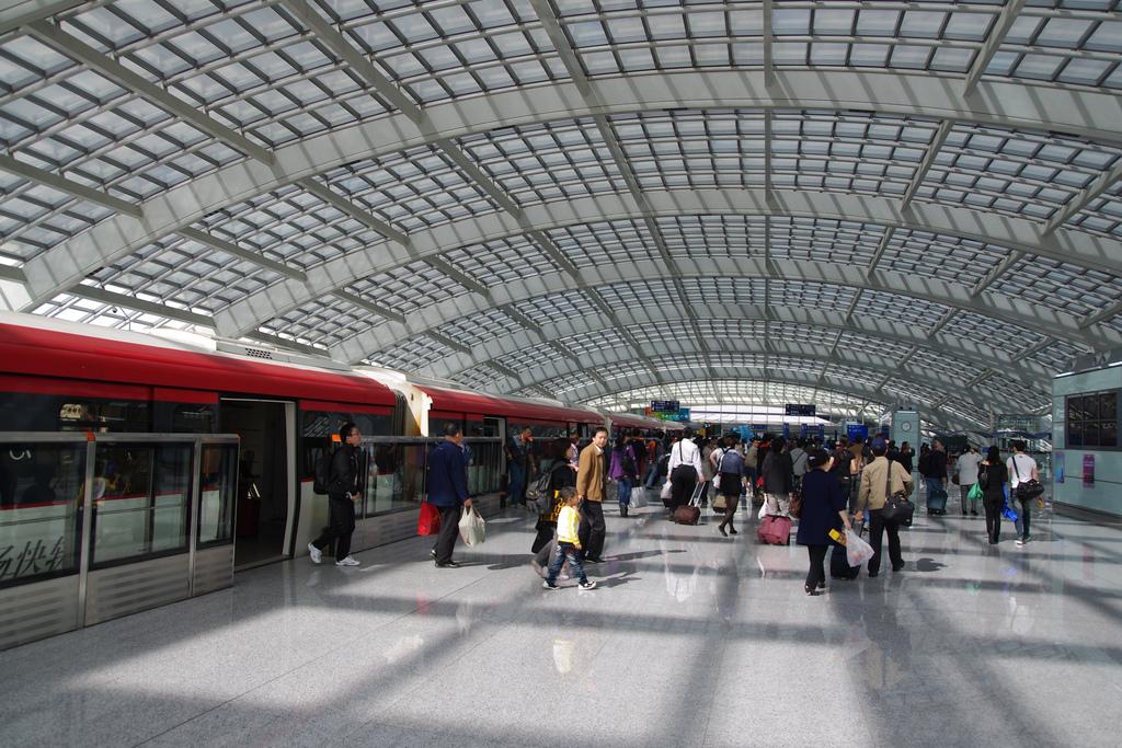 Penumpang meninggalkan kereta penghubung di Bandara Internasional Beijing Capital, RRC. (Foto oleh Chinnian/Flickr)