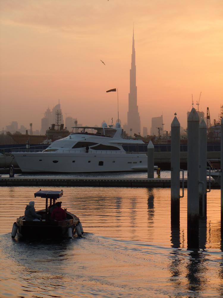 Kapal mewah di Marina Dubai dengan latar belakang Burj Khalifa, gedung tertinggi di dunia.