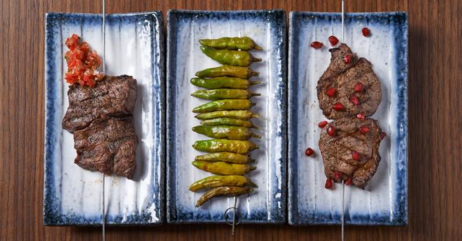 Sajian sate dry-aged beef, shishiito peppers, dan daging sapi tenderloin dry-aged di Chambers Bar & Grill.