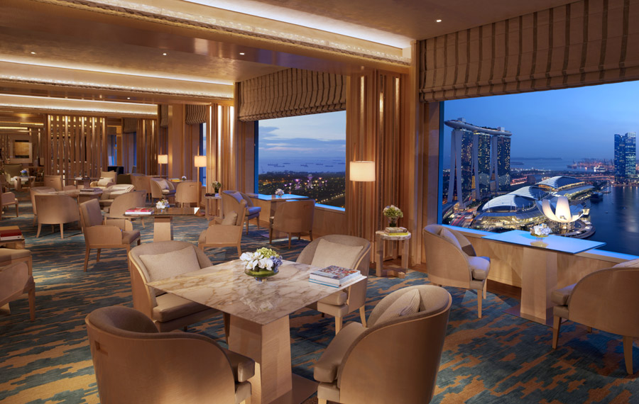 Ruang duduk Club Lounge dengan jendela-jendela besar menampilkan panorama kota Singapura.