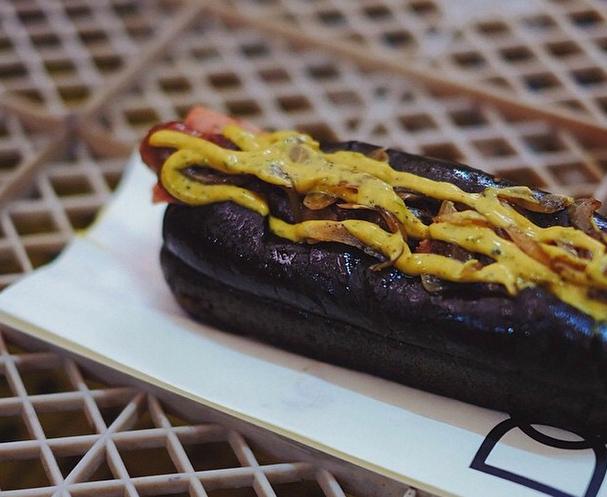Hotdog di Dudes of Gourmet dengan roti berwarna hitam pekat. (Foto: Instagram/diyoji)