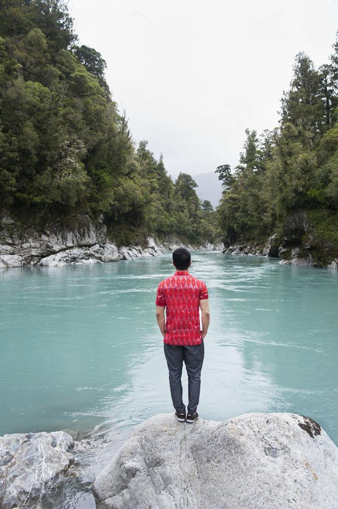 Air yang membawa deposit gletser di Hokitika Gorge. (Kemeja lengan pendek dan celana oleh Ikat Indonesia by Didiet Maulana)