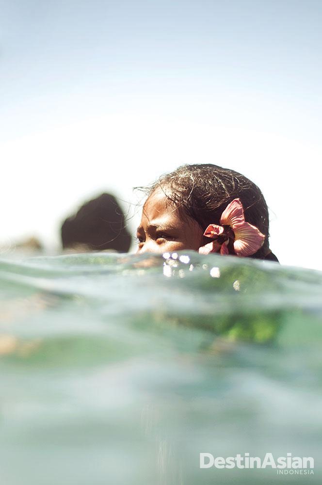 Seorang gadis cilik tengah bermain di pantai. Pantai-pantai di Banda dianugerahi air berwarna turkuois dan pasir putih.