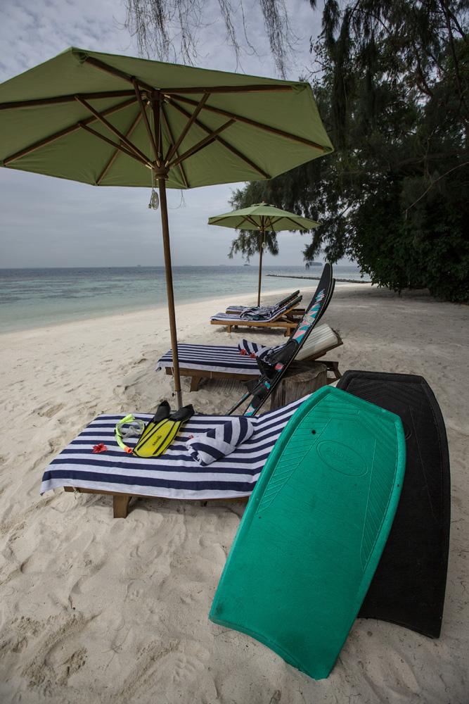 Peralatan snorkeling, ski air dan boogieboard di depan pantai resor.
