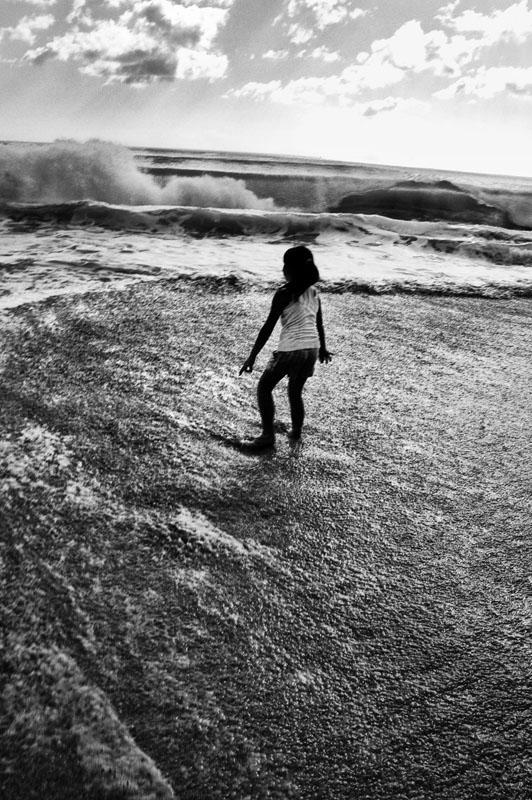 Seorang gadis kecil bermain di pantai.