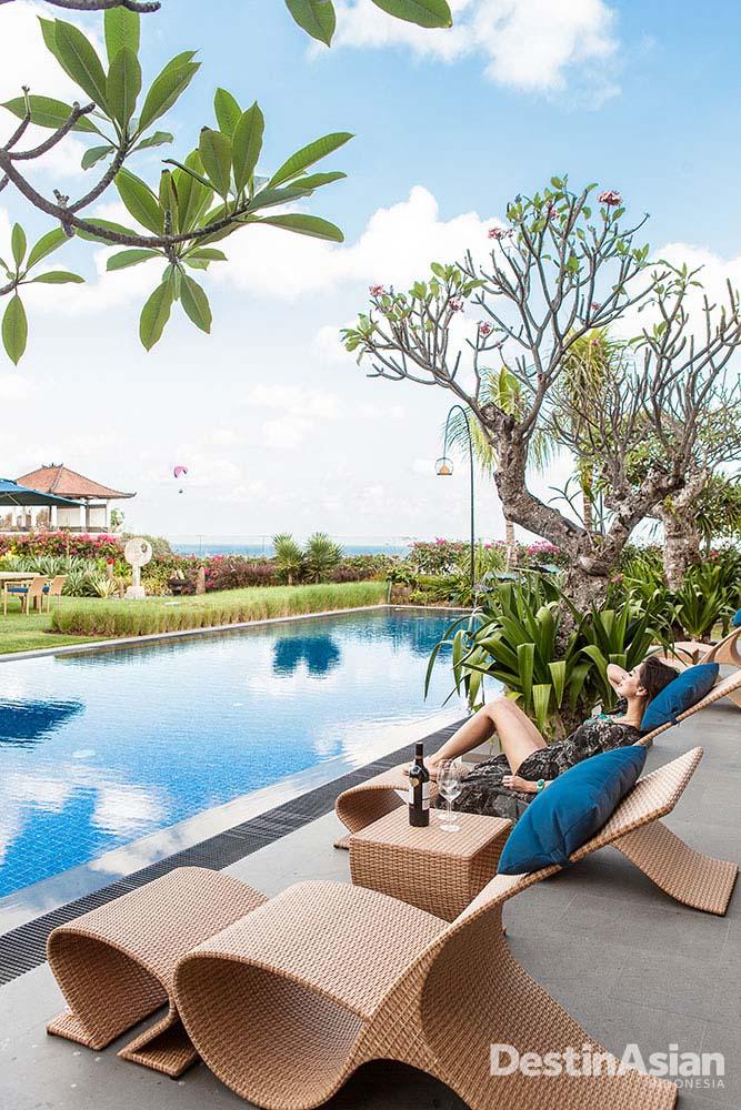 Area bersantai di tepi kolam renang Villa Frangipani dengan pemandangan menawan.