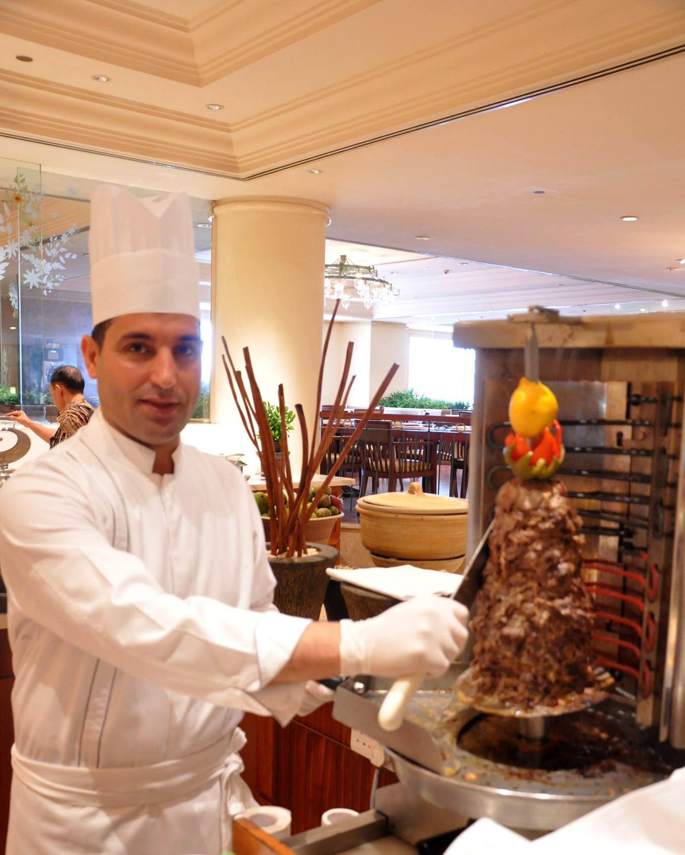 Salah satu koki sedang menyiapkan shawarma.