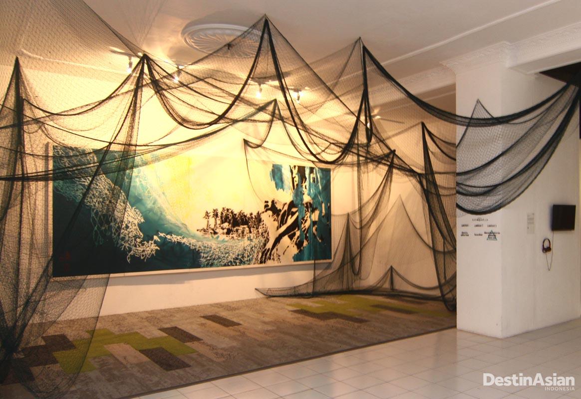 Instalasi seni berjudul 'Net Impact' kreasi KA'a yang menggabungkan lukisan, cat semprot, instalasi, jala ikan, serta proyeksi video.