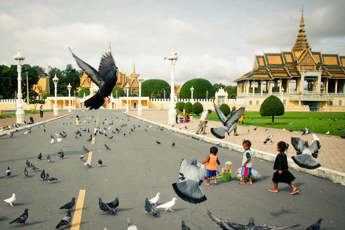 Aktivitas gratis favorit anak-anak Kamboja di depan Royal Palace: bermain dengan kawanan burung