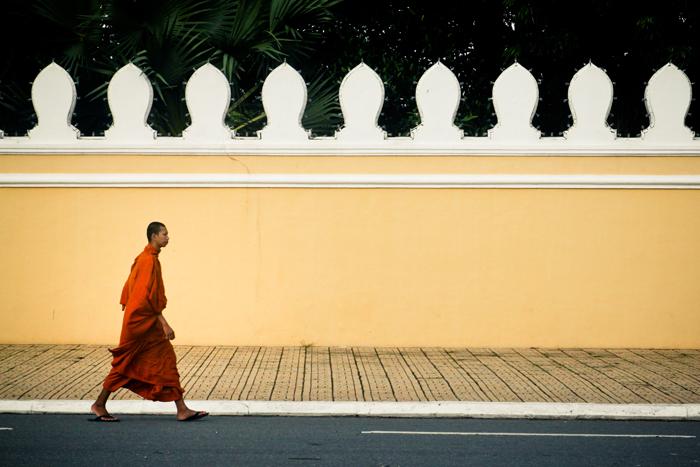 Seorang biksu berjalan di luar tembok kompleks istana. Potret jamak di Phnom Penh.
