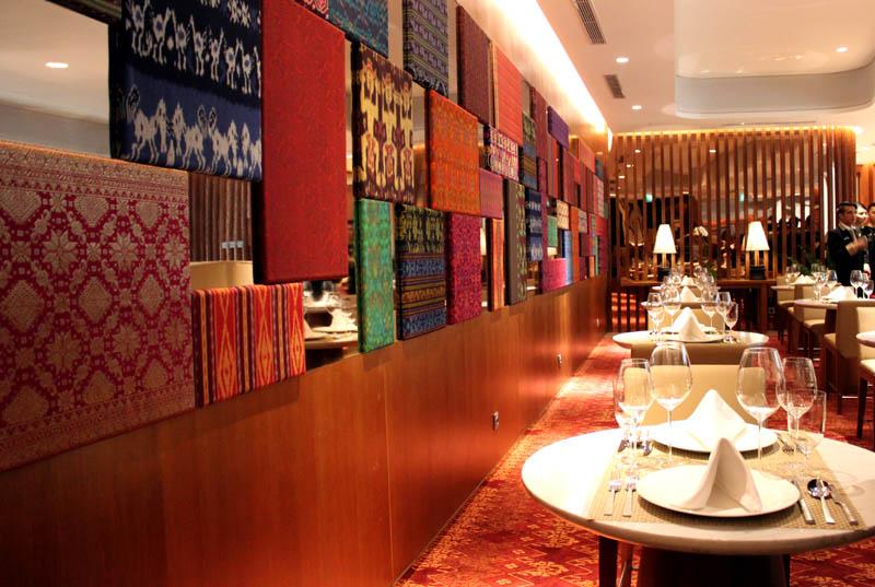 Ruang makan di area first class dengan hiasan dinding kain tradisional Indonesia.
