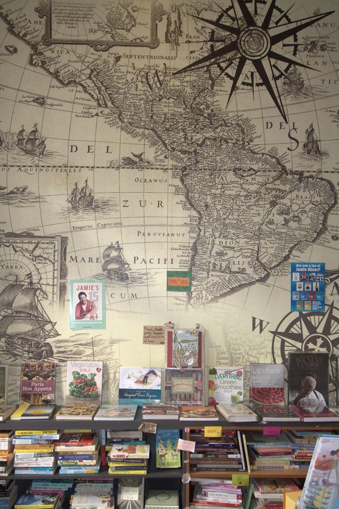 Rak berisi buku-buku travel di Littered With Books.