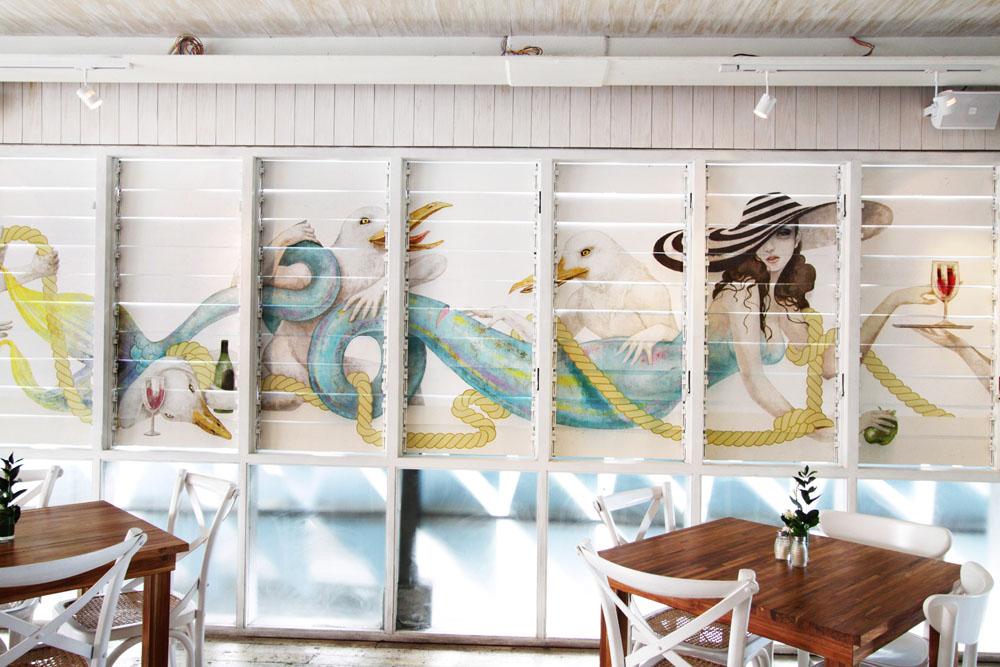 Mural imajinatif di dinding Meja Kitchen & Bar.