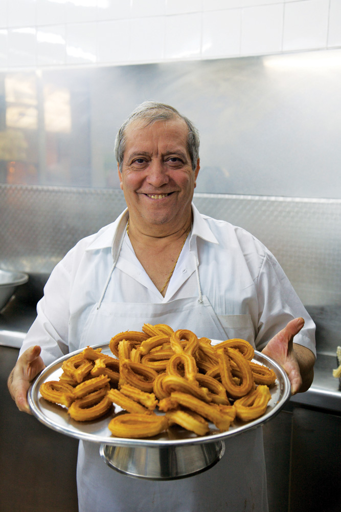 Manuel San Roman menyuguhkan tumpukan churro (donat Spanyol).
