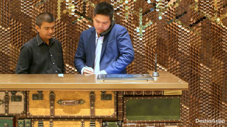Meja resepsionis yang terbuat dari susunan koper lawas.
