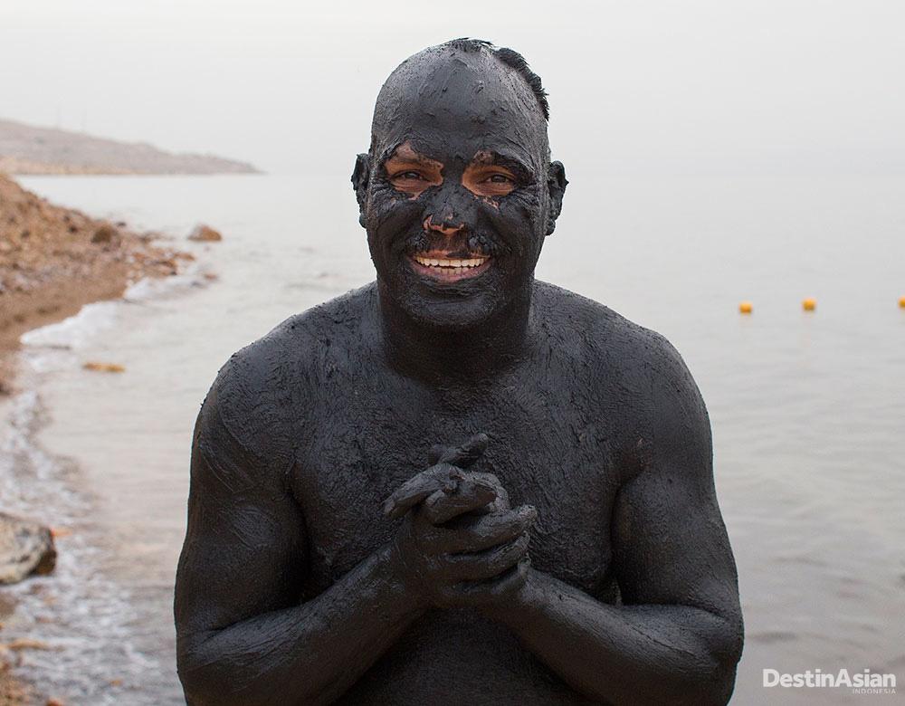 Salah seorang turis usai berendam di lumpur hitam di tepi Laut Mati. Konon, lumpur itu memiliki khasiat medis.