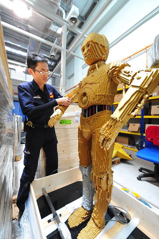 Salah seorang seniman tengah membangun robot C-3PO di Legoland Malaysia.