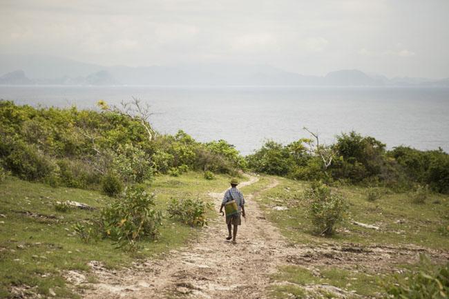 Seorang penggembala di Tanjung Rait dengan pemandangan Sumbawa di kejauhan, di seberang Selat Alas.
