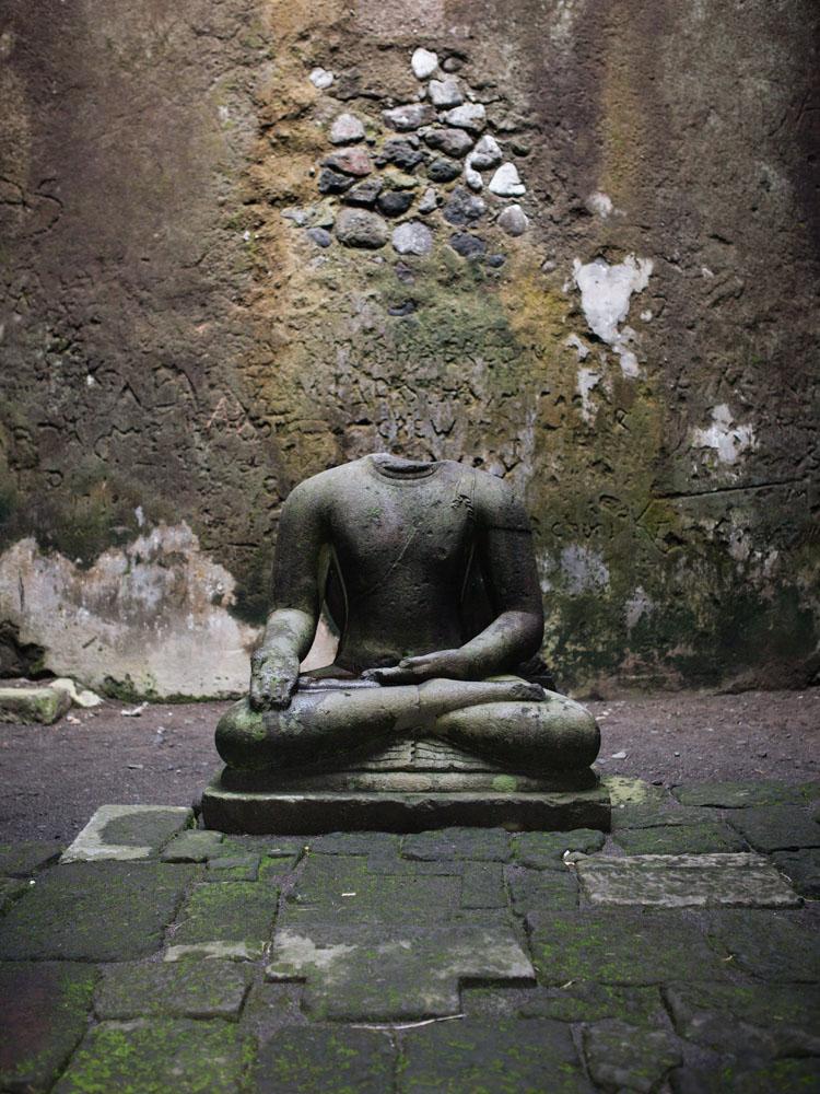 Patung Budha tanpa kepala di Candi Ngawen. Rusak terhantam serangan alam.