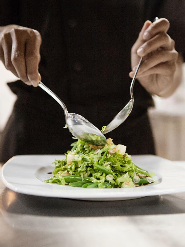 Sang koki menyiapkan salad untuk sarapan di restoran Java Red, MesaStila.