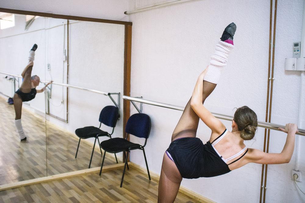 Seorang penari melakukan peregangan sebelum mulai latihan.