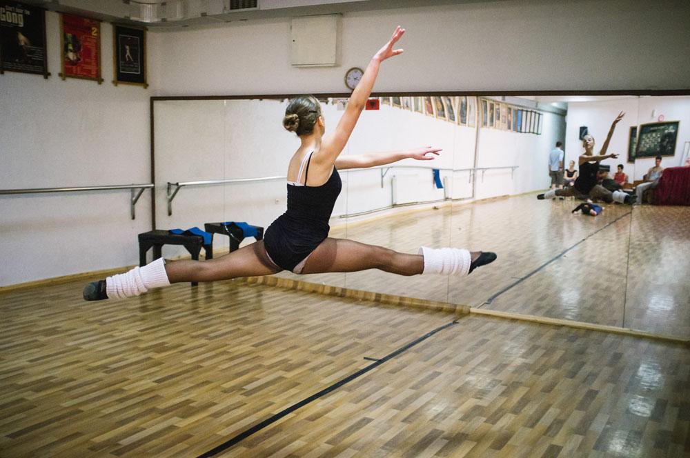 Seorang penari wanita melakukan lompatan bagian dari latihan di studio.