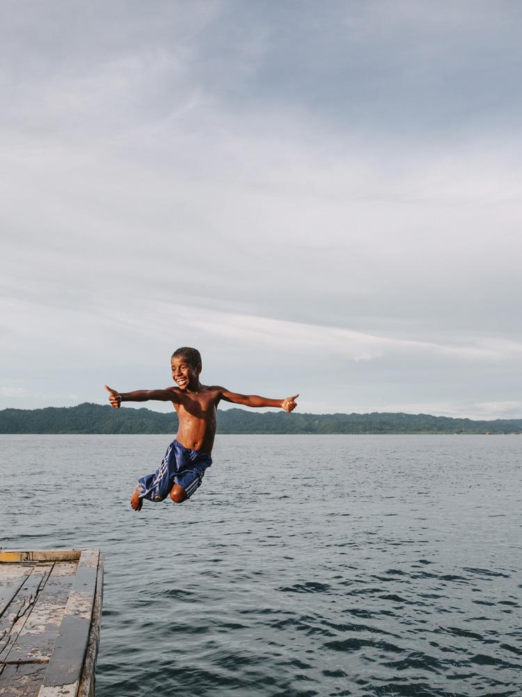 Seorang anak kecil bermain di dermaga Arborek.