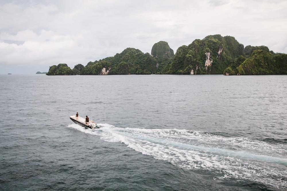Kapal cepat kecil membelah laut di titik selam di sekitar Farondi, Misool.
