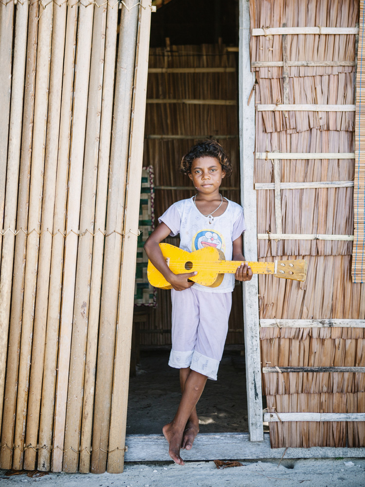 Seorang gadis cilik lokal dengan ukulele buatan sendiri di Arborek, Raja Ampat.