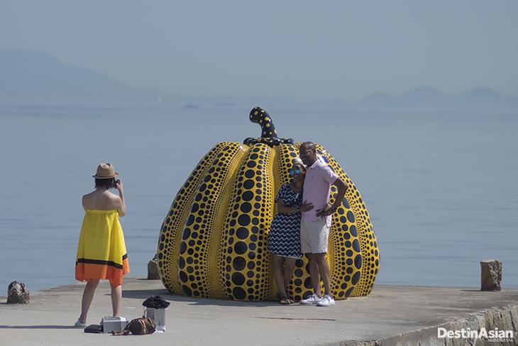 Pengunjung berfoto dengan latar labu kuning dengan bintik hitam (Pumpkin) karya Yayoi Kusama