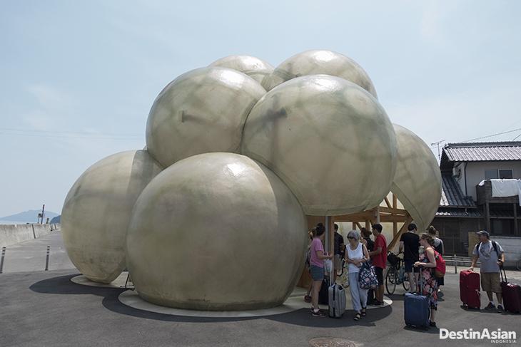 Wisatawan berkumpul di bangunan yang digunakan sebagai tempat parkir motor dan sepeda di Pelabuhan Honmura, Naoshima, Jepang.