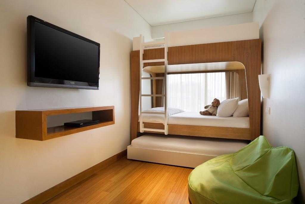 Kamar tidur anak dengan tempat tidur tingkat, bean bag, TV layar datar, serta pemutar DVD.