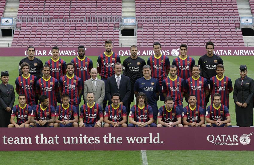 Petinggi Qatar Airways dan FC Barcelona sedang berfoto dengan para pemain tim tersebut.