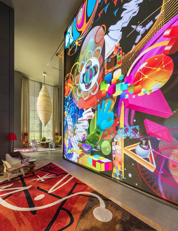 Video wall yang menampilkan karya seni warna-warni.